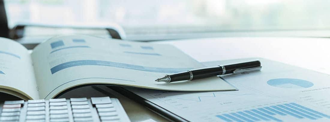 Mesa con papeles, calculadora y boli