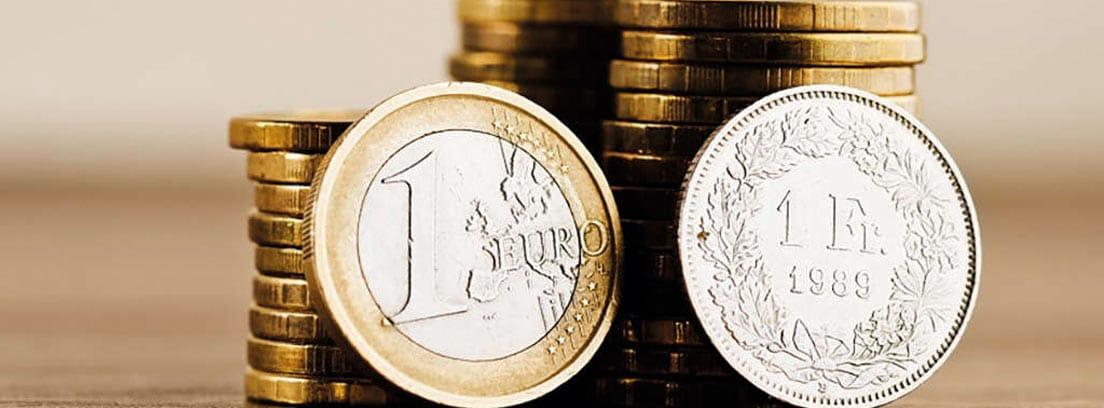 Dos monedas delante de varias columnas de monedas