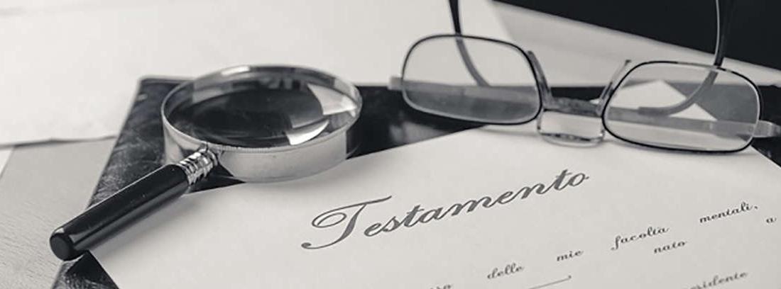 Lupa y gafas sobre un documento de testamento