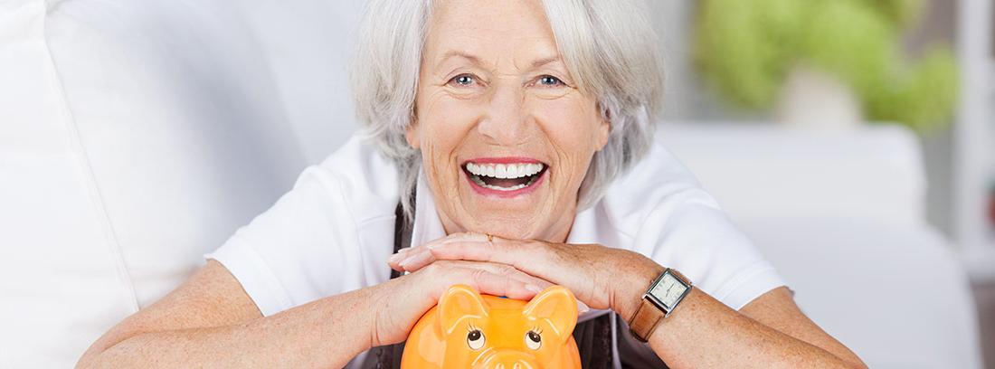 Mujer sonriente apoyada en una hucha de color naranja