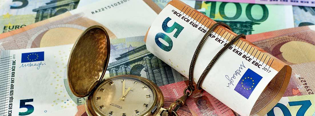 Varios billetes en una mesa con un reloj que sostiene uno de 50 euros