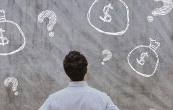 Hombre de espaldas mirando una pared con dibujos de sacos de dinero e interrogaciones