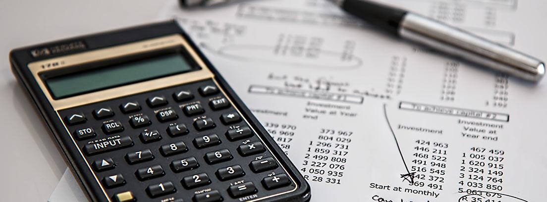 Calculadora y boli sobre unos papeles con números