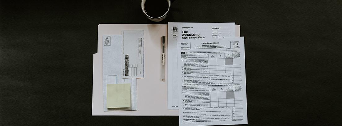 Diferentes papeles, cartas, sobres y facturas sobre una mesa junto a una taza