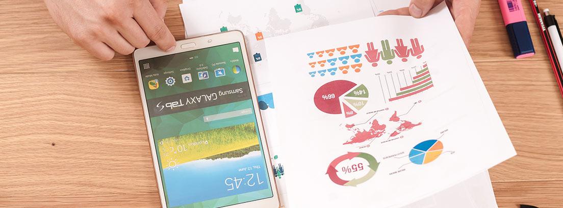 Manos con papeles con gráficos y una tableta pequeña