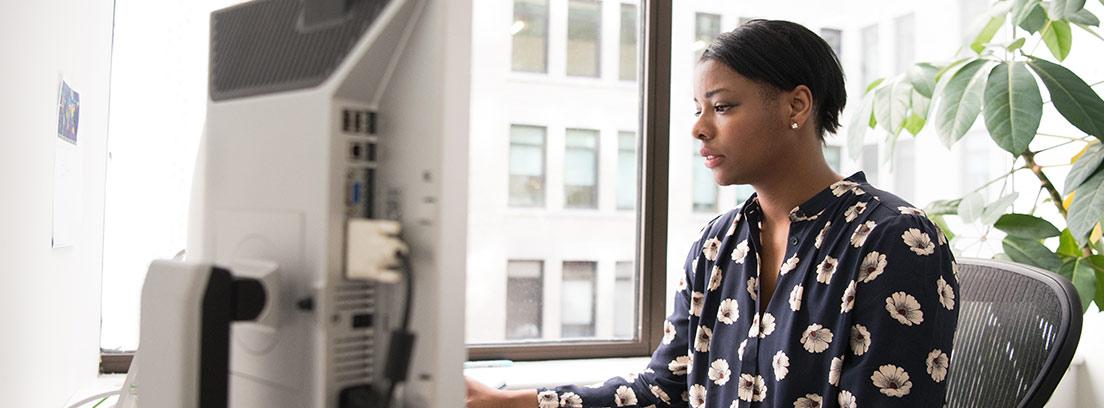 Mujer sentada delante de mesa de trabajo con teclado y monitor