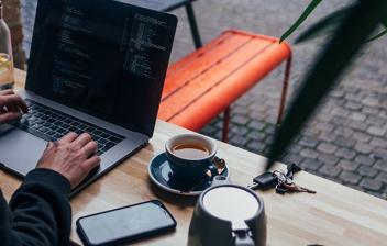 Persona sentada tecleando ordenador portátil junto a taza y tetera