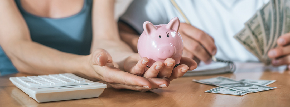 Hombre y mujer con dinero, una hucha de cerdo y una calculadora