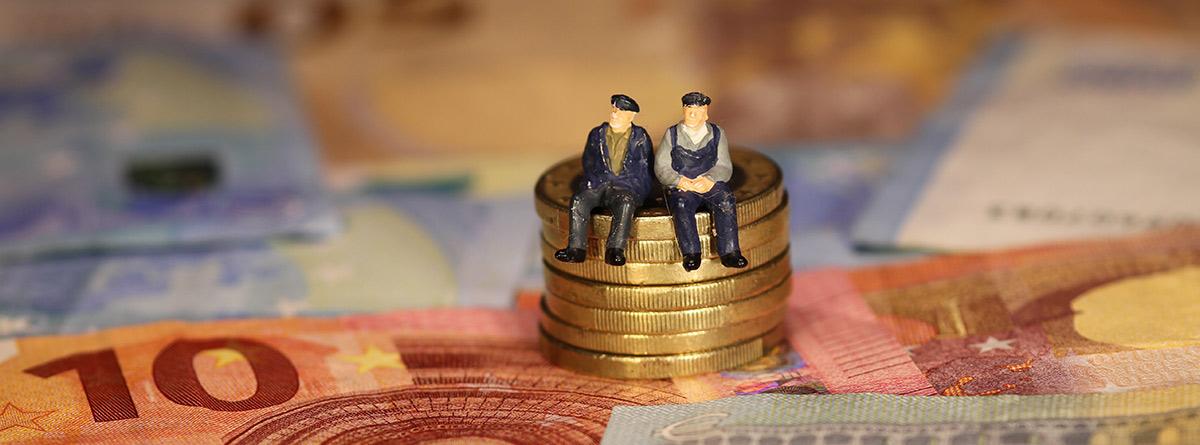 Figuras de dos personas mayores sobre monedas y billetes de Euro