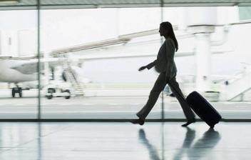 Mujer emprendedora con una maleta por un pasillo de un aeropuerto