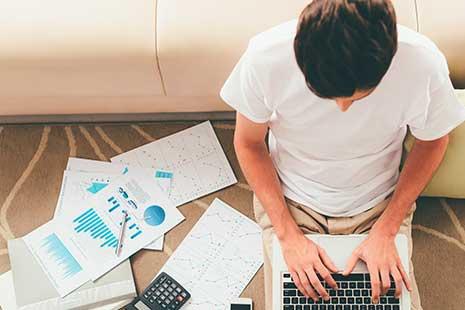 Autónomo trabaja en casa con portátil, móvil y calculadora