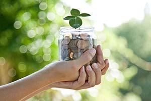 Un tarro con monedas del que emerge una pequeña planta