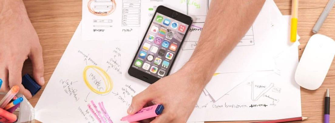 Vista cenital de unas manos sobre una mesa con papeles y un móvil