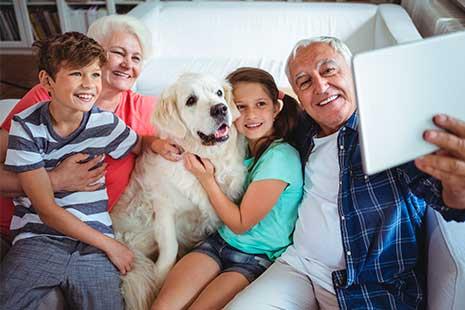 Abuelos posan con sus nietos y su mascota para selfie con tablet