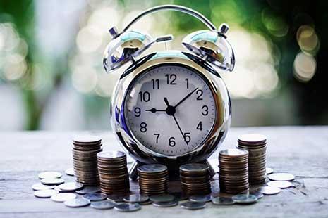 Reloj despertador rodeado de montones de monedas