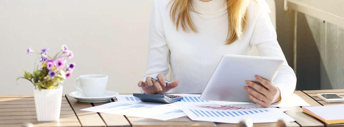 Mujer con papeles, tablet y calculadora