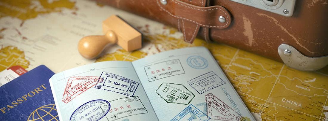 Pasaporte con sellos sobre un mapa del mundo.