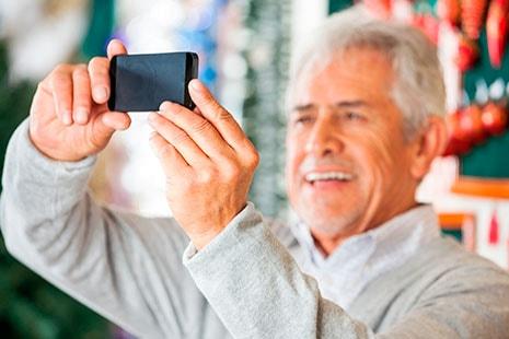 Hombre mayor sostiene un teléfono móvil frente a su cara.