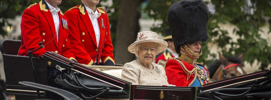 Reina Isabel II con chaqueta rosa, gorro y guantes.