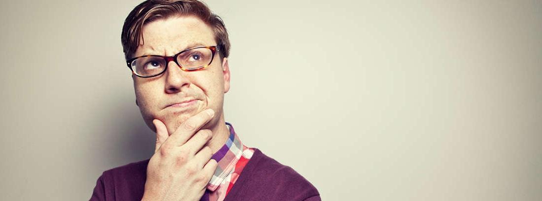Hombre maduro piensa con camisa blanca y gafas