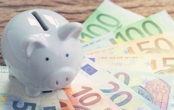 Hucha con forma de cerdo sobre unos billetes de euro
