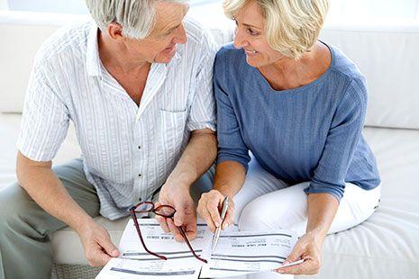 Hombre y mujer maduros mirándose y sosteniendo papeles.