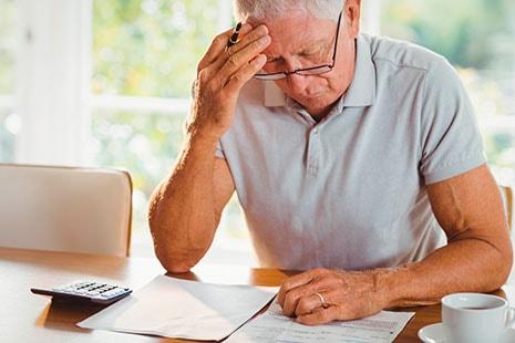 Hombre mayor se toca la sien sentado frente a una mesa con papeles