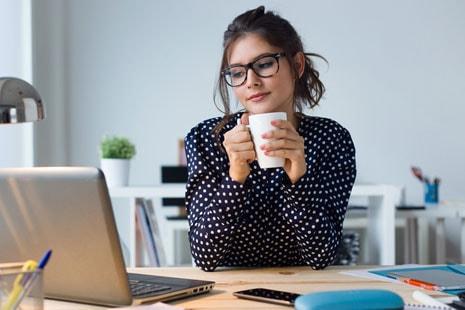 Mujer joven delante de ordenador portátil y con una taza entre las manos.