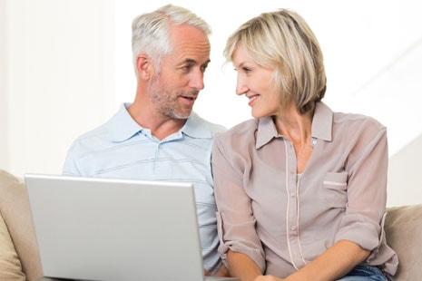 Hombre y mujer maduros sentados en un sillón con un ordenador portátil frente a ellos.