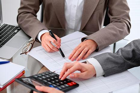 Dos personas haciendo cálculos con una calculadora