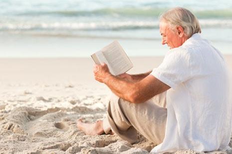 Hombre mayor sostiene entre sus manos un libro.