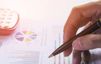 Mano sosteniendo un bolígrafo sobre un folio con esquemas