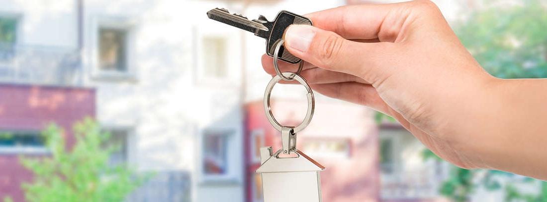 Hombre y mujer dándose un apretón de manos al firmar un contrato referente a una casa