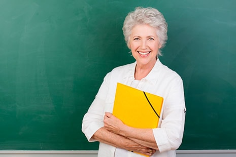 Alt Anciana con una carpeta amarilla enfrente de una pizarra