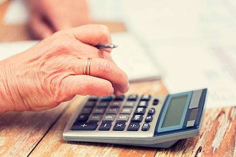 Mano envejecida teclea los números de una calculadora