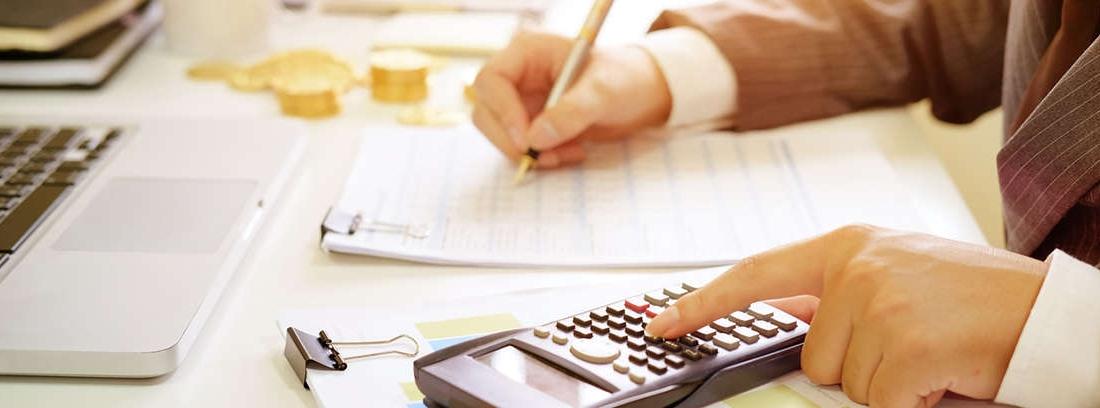 Mano con bolígrafo apuntando sobre un cuaderno.