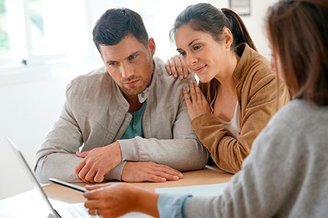 Hombre y mujer jóvenes miran hacia pantalla