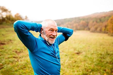 Hombre de edad avanzada con manos detrás de la cabeza y de pie.