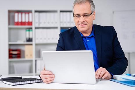Hombre de mediana edad frente a un ordenador portátil