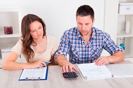 Hombre y mujer frente a papeles y con calculadora