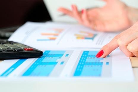 Mano de mujer señalando sobre papeles con números
