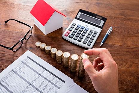 Mano colocando una moneda en una columna con calculadora y papeles