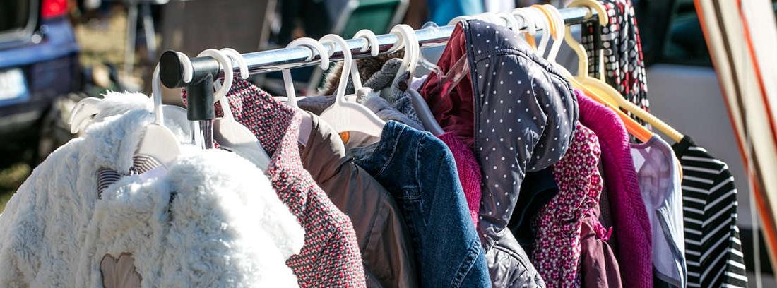 Mujer joven delante de un perchero de ropa