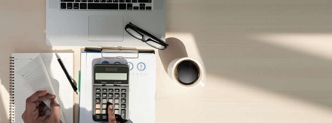 Hombre con calculadora en la mano y apuntando en papel
