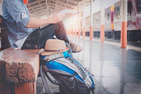 Hombre consultando plano junto a su mochila en estación de tren