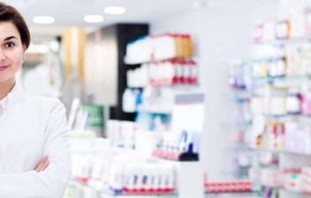 Mujer con bata cruzada de brazos en una farmacia