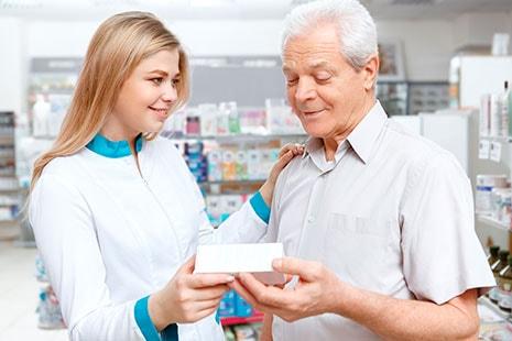 Chica joven con bata blanca ofrece caja de medicamento a un hombre mayor