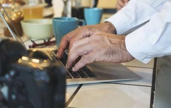 Señora sonriente y delante de pantalla de ordenador portátil