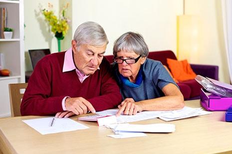 Hombre y mujer mayores mirando papeles y usando calculadora