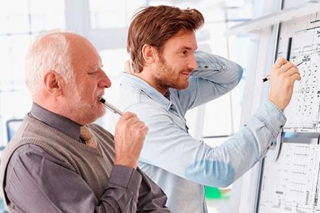 Hombre mayor junto a joven mirando un tablero con planos